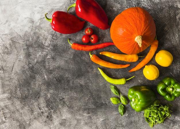 Uma visão aérea de vegetais orgânicos frescos no plano de fundo texturizado Foto gratuita