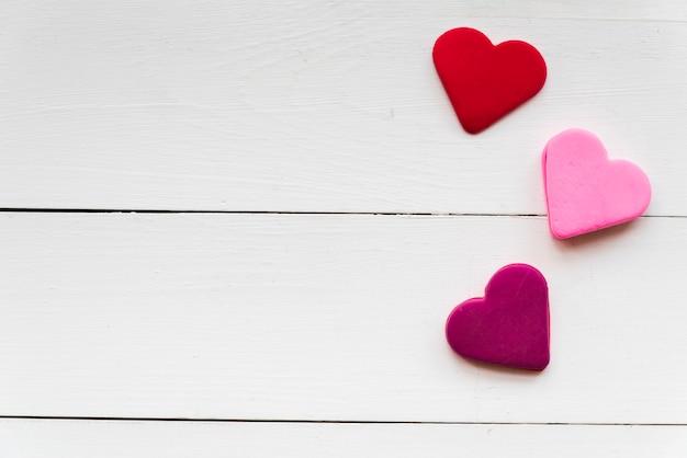 Uma visão aérea de vermelho; formas de coração-de-rosa e roxas na mesa texturizada branca Foto gratuita