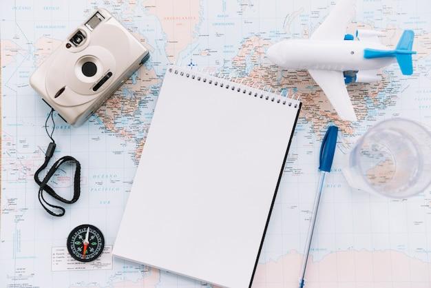 Uma visão aérea do avião branco em miniatura; bloco de notas espiral em branco; caneta; câmera e bússola no mapa Foto gratuita