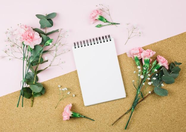 Uma visão aérea do bloco de notas em espiral cercado com gypsophila e cravo flores em fundo duplo rosa e papelão Foto gratuita