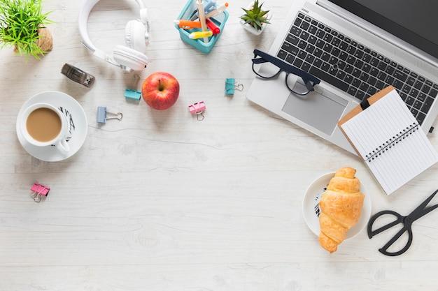 Uma visão aérea do café da manhã com material de escritório e laptop na mesa de madeira Foto gratuita