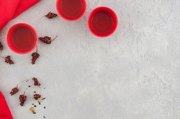 Uma visão aérea do copo de chá tradicional vermelho com ervas no pano de fundo texturizado cinza Foto gratuita