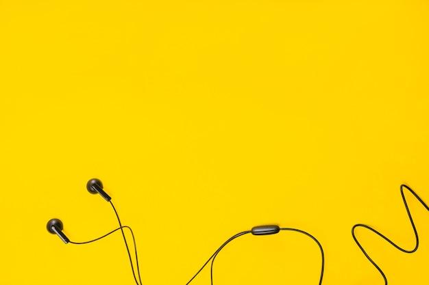 Uma visão aérea do fone de ouvido no fundo amarelo com espaço para texto Foto gratuita