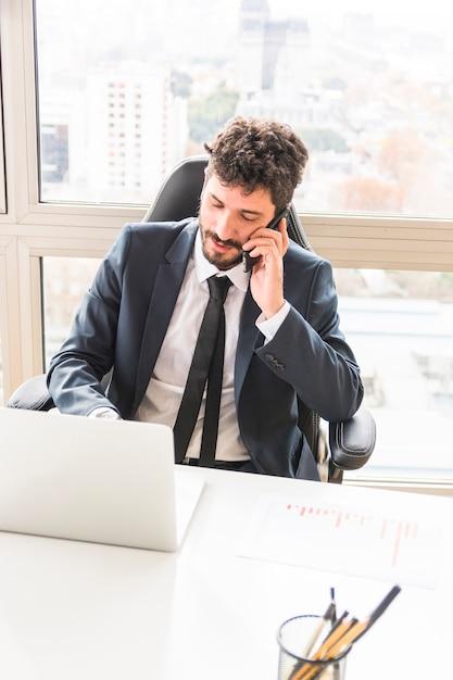 Uma visão aérea do jovem empresário falando no celular no local de trabalho Foto gratuita