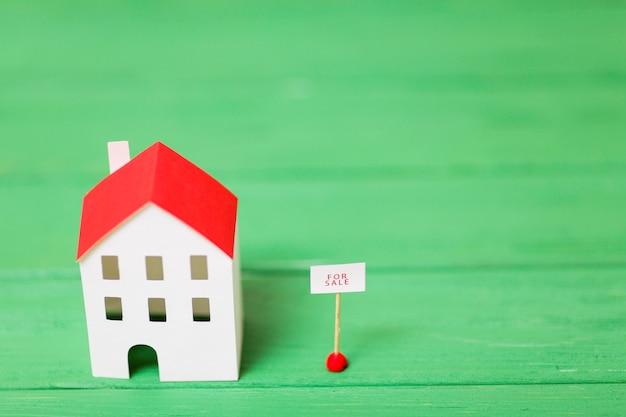 Uma visão aérea do modelo de casa em miniatura perto da marca de venda em plano de fundo texturizado verde Foto gratuita