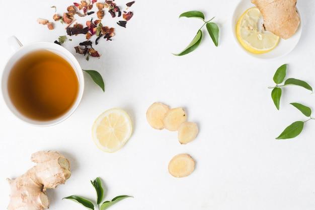 Uma visão elevada da xícara de chá de ervas com limão; gengibre e ervas secas em pano de fundo branco Foto gratuita