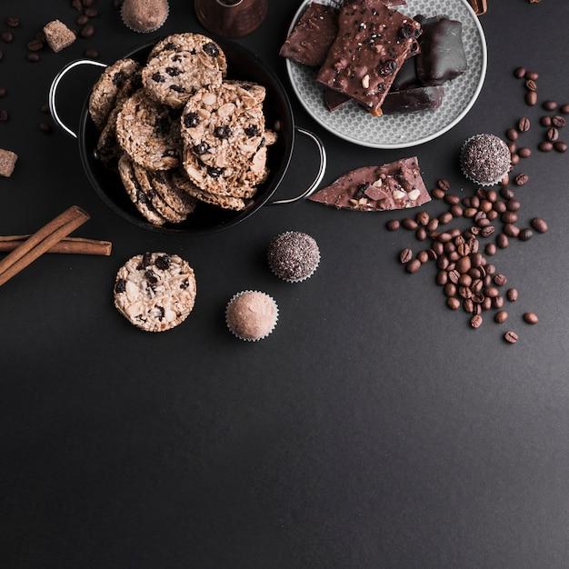 Uma visão elevada de canela; biscoitos; trufas de chocolate e grãos de café sobre fundo preto Foto gratuita
