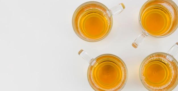 Uma visão elevada de chá de gengibre em copos de vidro no fundo branco Foto gratuita