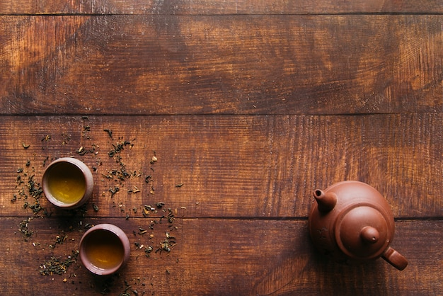 Uma visão elevada de panela de barro com xícaras de chá de ervas na mesa de madeira Foto gratuita