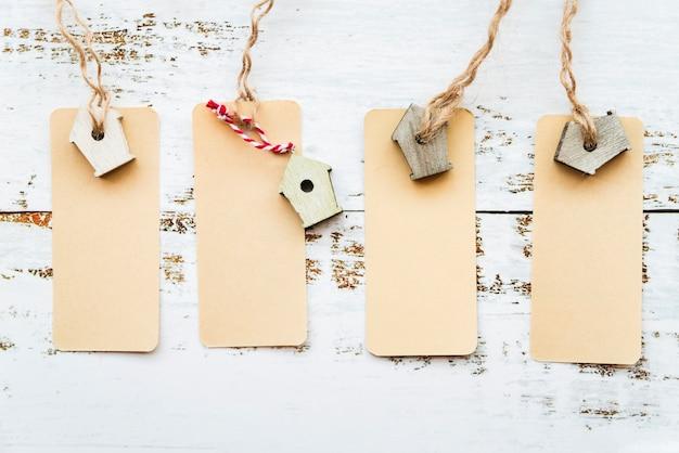 Uma visão elevada de tags com birdhouse em miniatura na mesa branca Foto gratuita