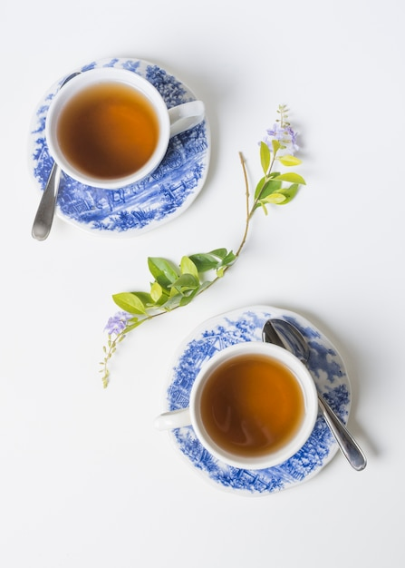 Uma visão elevada de xícaras de chá de porcelana de ervas em pires com galho de limão no fundo branco Foto gratuita