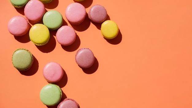 Uma visão elevada do amarelo; macaroons de rosa e verdes sobre fundo colorido Foto gratuita