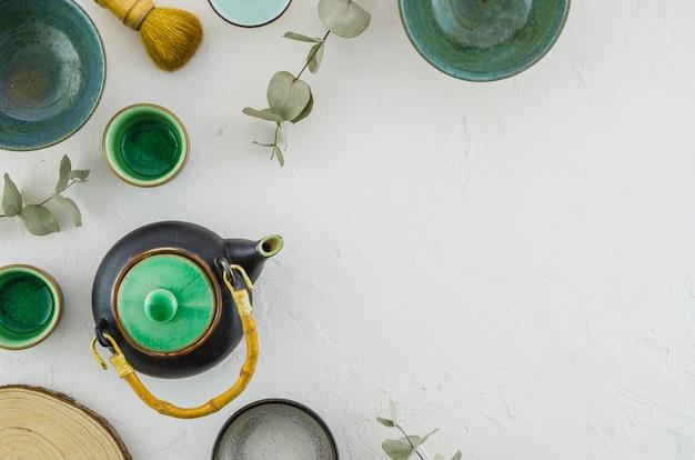 Uma visão elevada do bule; tigela; xícara de chá; escova isolada no pano de fundo branco Foto gratuita