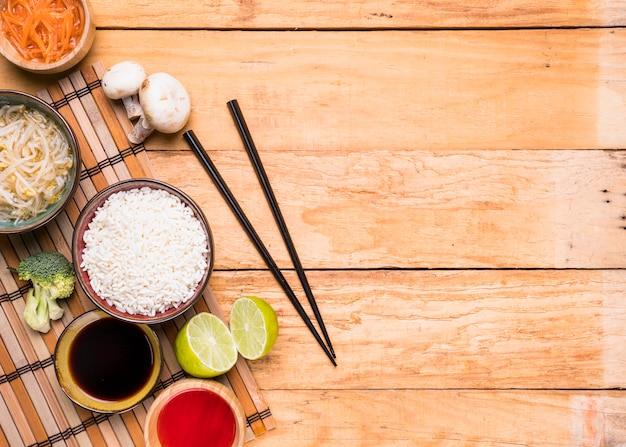 Uma visão elevada do cogumelo; brotar feijão; arroz; brócolis; limão; e molho com pauzinhos contra mesa de madeira Foto gratuita