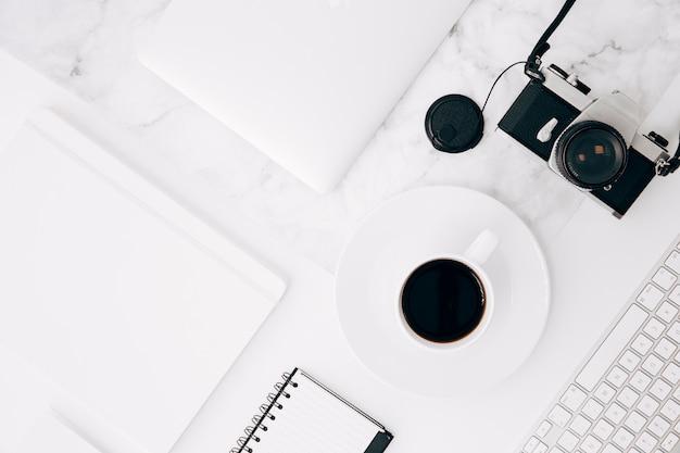 Uma visão elevada do diário; tablet digital; xícara de café; câmera e teclado na mesa Foto gratuita