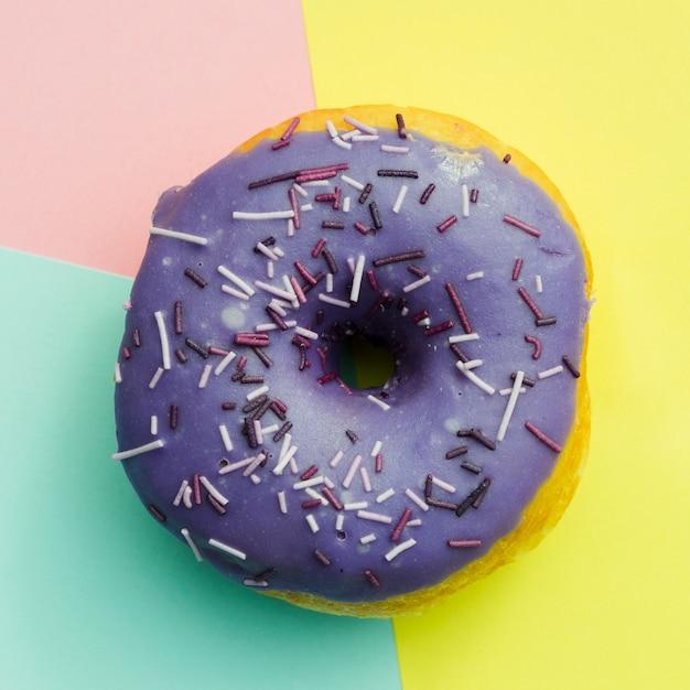 Uma visão elevada do donut roxo com granulado em fundo colorido Foto gratuita