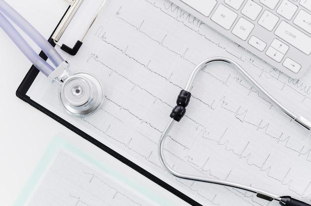 Uma visão elevada do estetoscópio sobre o relatório médico ecg perto do teclado Foto gratuita