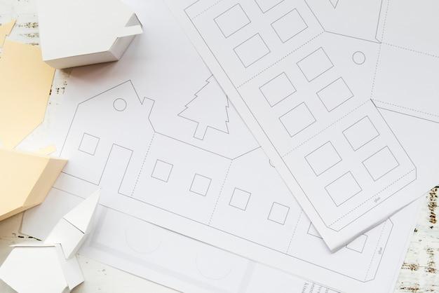 Uma visão elevada do modelo de casa de papel criativo e livro branco na mesa Foto gratuita