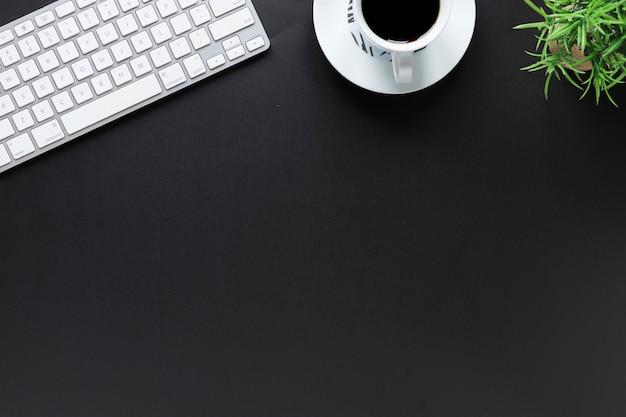 Uma visão elevada do teclado; xícara de café; e vaso de plantas em fundo preto com espaço de cópia Foto gratuita