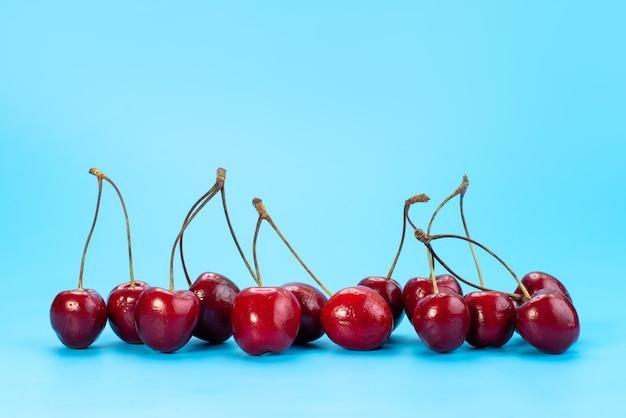 Uma visão frontal das cerejas vermelhas frescas maduras e azedas no azul, cor de frutas do verão Foto gratuita
