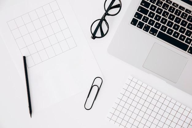 Uma visão geral da página; lápis; clipe de papel; óculos e laptop em fundo branco Foto gratuita