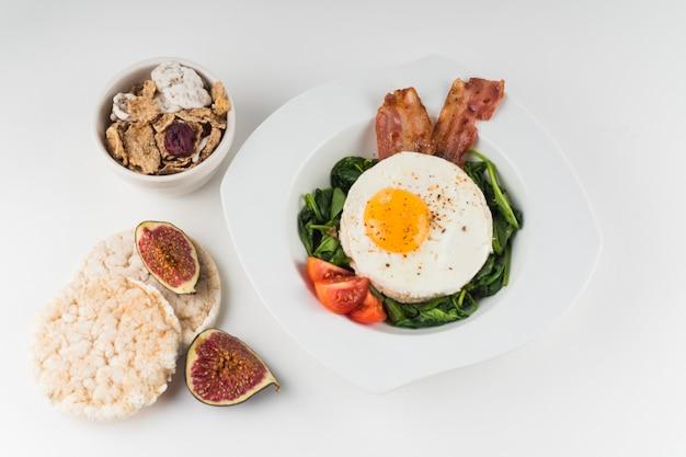 Uma visão geral de flocos de milho; bolacha de arroz; prato de figo e ovo frito, isolado no fundo branco Foto gratuita