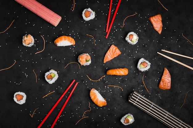 Uma visão geral de placemat enrolado; pauzinhos; sushi; fatia de salmão; cenoura ralada; sementes de gergelim e pauzinhos vermelhos sobre fundo preto Foto Premium