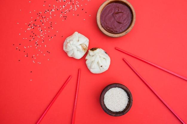 Uma visão geral do molho; dumplings; sementes de gergelim e pauzinhos no pano de fundo vermelho Foto gratuita