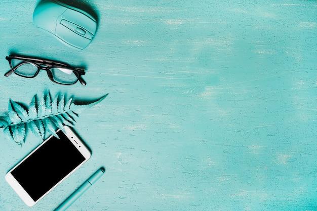 Uma visão geral do mouse; óculos; folhas de samambaia artificial; smartphone e caneta em fundo turquesa Foto gratuita