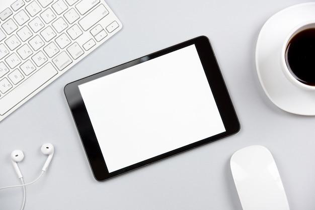 Uma visão geral do teclado; fone de ouvido; rato; tablet digital e xícara de café sobre fundo cinza Foto gratuita