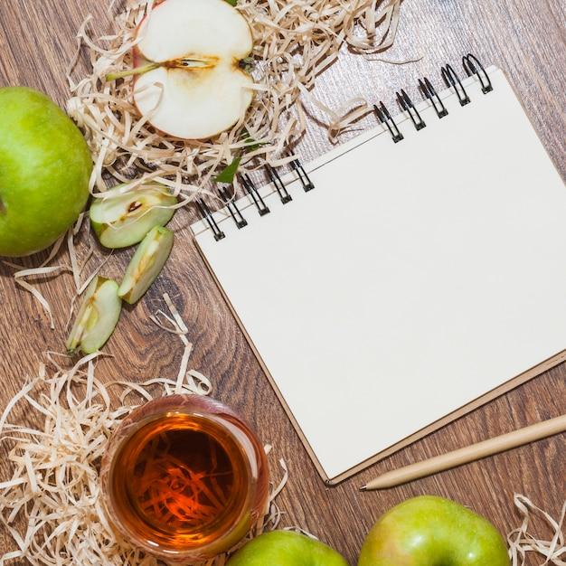 Uma visão geral do vinagre de maçã; maçãs verdes e bloco de notas em espiral com lápis na mesa de madeira Foto gratuita