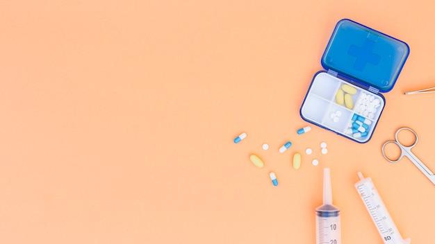 Uma vista aérea da caixa de comprimidos médicos; seringa; tesoura e pinça em fundo bege Foto gratuita