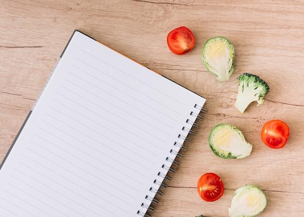 Uma vista aérea do caderno espiral com couves-de-bruxelas; tomates e brócolis na mesa de madeira Foto gratuita