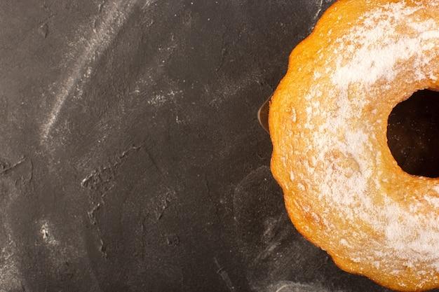Uma vista de cima assada em um bolo redondo com açúcar em pó no fundo de madeira Foto gratuita