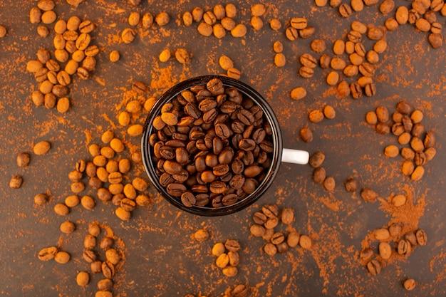 Uma vista de cima com sementes de café marrom dentro da tigela na mesa marrom Foto gratuita