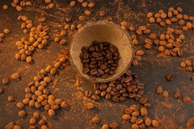 Uma vista de cima com sementes de café marrom dentro e fora da casca do coco na mesa marrom Foto gratuita