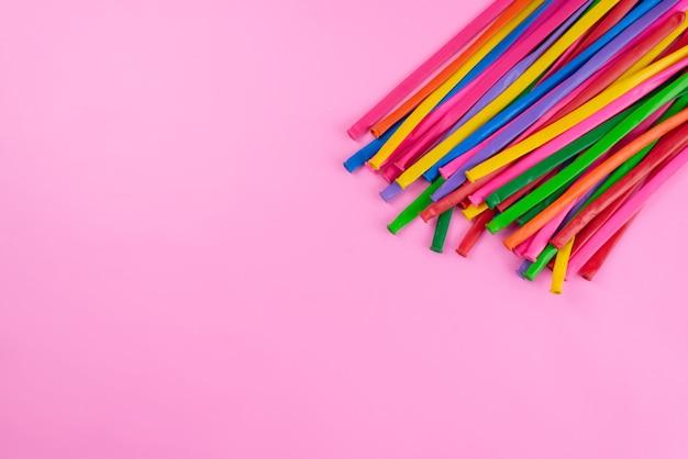 Uma vista de cima em bastões coloridos longos e palha parecidos com rosa, composição de fotos coloridas Foto gratuita