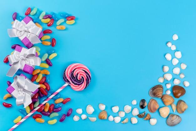 Uma vista de cima, pirulitos e geleias coloridas doces junto com conchas do mar no azul, confeitaria doce de açúcar Foto gratuita