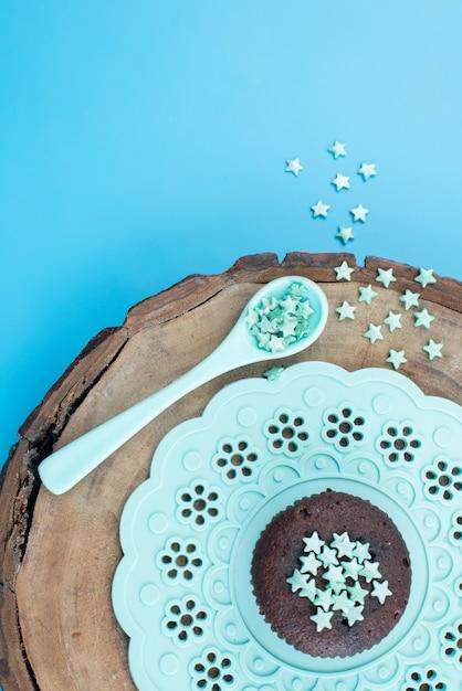 Uma vista de cima. uma pequena estrela assina de cor verde em uma estrela de decoração de madeira marrom Foto gratuita