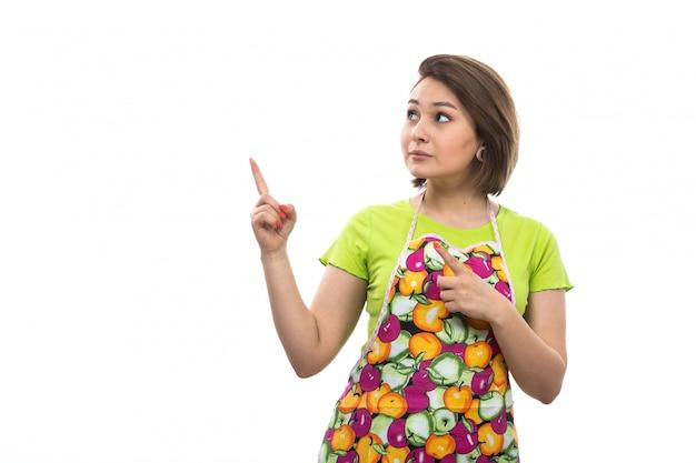 Uma vista dona de casa bonita nova na camisa verde que levanta colorido da camisa surpreendeu hesitou olhando na expressão dos céus no fundo branco casa cozinha fêmea Foto gratuita