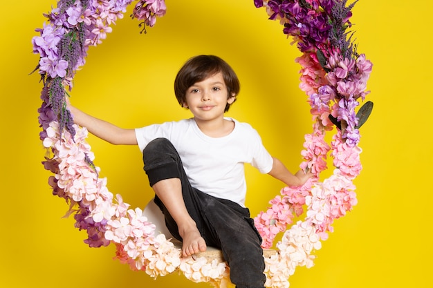 Uma vista frontal adorável menino bonitinho na camiseta branca sobre a mesa amarela Foto gratuita