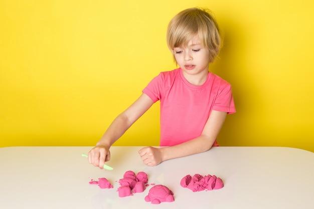 Uma vista frontal adorável menino bonitinho na camiseta rosa brincando com areia cinética colorida Foto gratuita