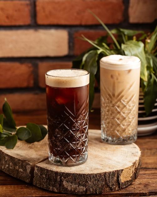 Uma vista frontal bebida alcoólica dentro de copos na mesa de madeira marrom Foto gratuita