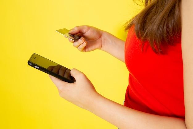 Uma vista frontal bela moça de camisa vermelha e calça jeans azul, segurando o telefone digitando o código Foto gratuita
