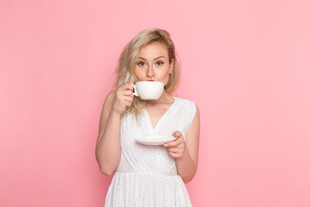 Uma vista frontal bela moça de vestido branco, bebendo um chá Foto gratuita