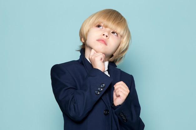 Uma vista frontal bonito rapaz de negócios em azul terno clássico posando sonhando pensando negócios trabalho moda Foto gratuita