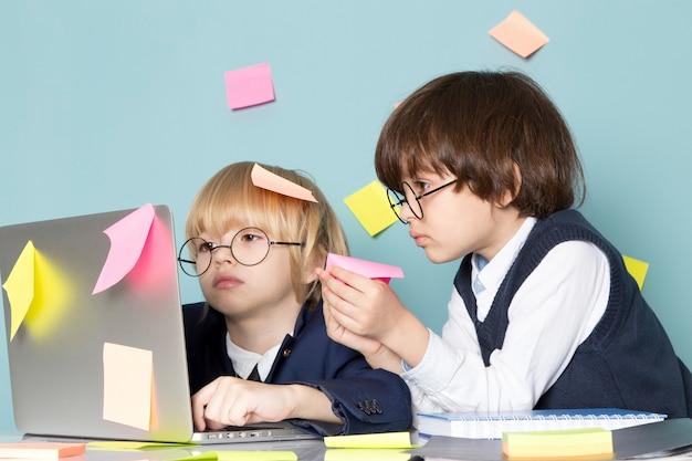 Uma vista frontal bonito rapaz de negócios em terno clássico azul posando na frente do laptop prata junto com outro garoto discutindo notas de colagem trabalhando negócios trabalho moda Foto gratuita