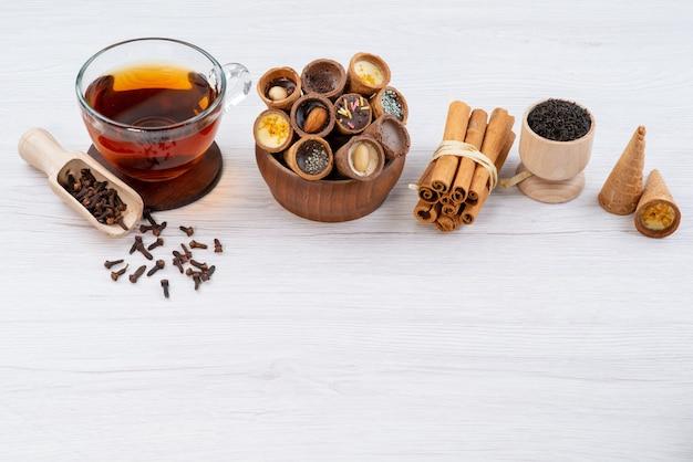 Uma vista frontal chifres e canela junto com uma xícara de chá branco, doce de bebida de sobremesa Foto gratuita