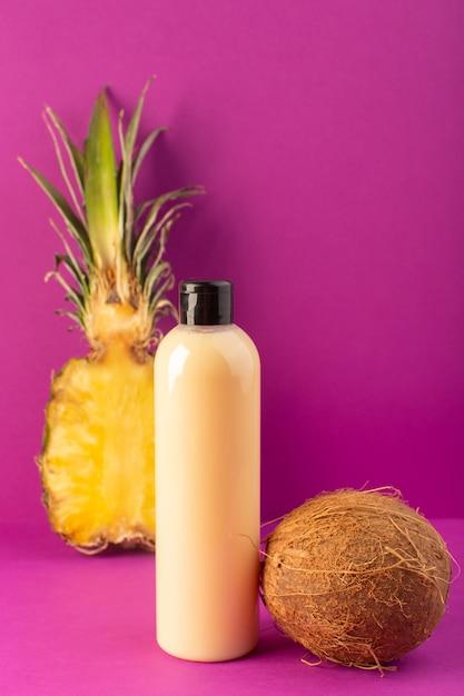Uma vista frontal creme shampoo de garrafa de plástico colorido pode com tampa preta junto com limões abacaxi e coco isolado no fundo roxo cosméticos beleza frutas Foto gratuita