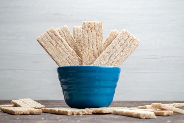 Uma vista frontal crocante dentro da tigela no fundo branco biscoito crocante seco Foto gratuita